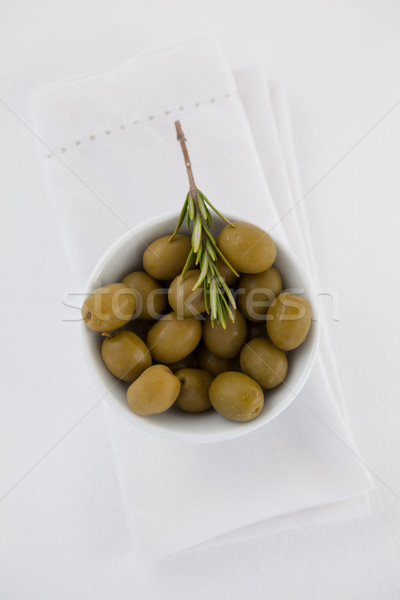 Overhead view of green olives with rosemary in bowl  Stock photo © wavebreak_media
