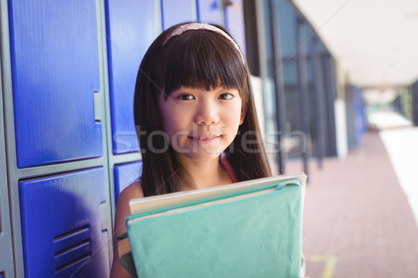 Portrait of elementary schoolgirl holding books in corridor Stock photo © wavebreak_media