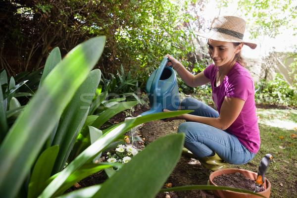 Glimlachende vrouw planten kan hurken Stockfoto © wavebreak_media