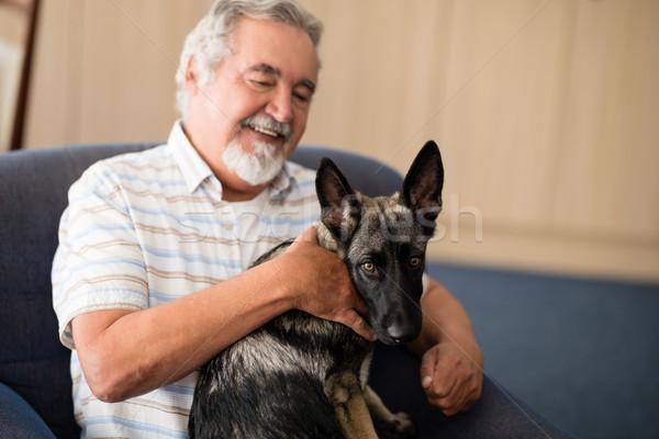 Happy senior man stroking puppy while sitting on armchair Stock photo © wavebreak_media