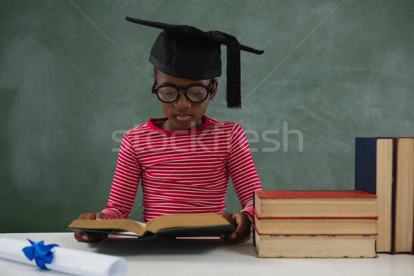 Schoolgirl in mortar board reading book against chalkboard Stock photo © wavebreak_media