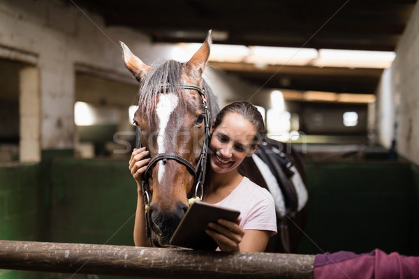 Smiling female jockey using digital tablet while standing by horse Stock photo © wavebreak_media