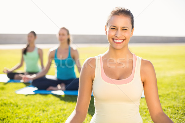 Smiling sporty brunette doing yoga with her friends Stock photo © wavebreak_media