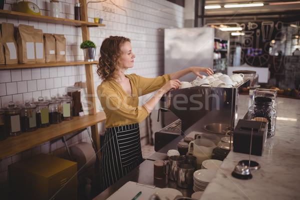 Young waitress arranging cups at counter Stock photo © wavebreak_media