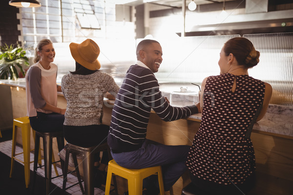 Cheerful young friends sitting table counter Stock photo © wavebreak_media