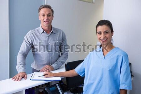 Portrait of smiling doctor holding pen standing by man at desk Stock photo © wavebreak_media