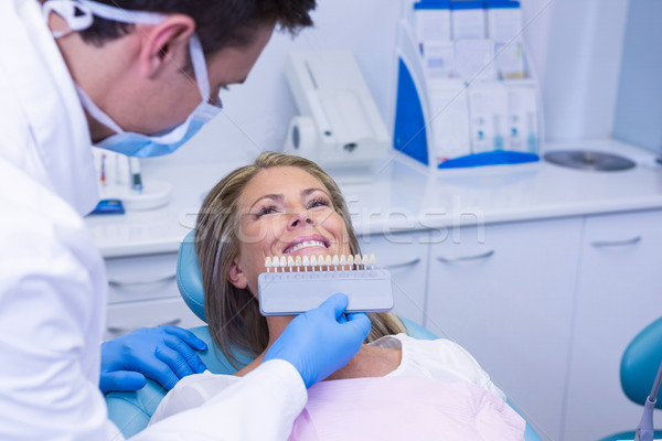 Doctor holding tooth whitening equipment by smiling patient Stock photo © wavebreak_media