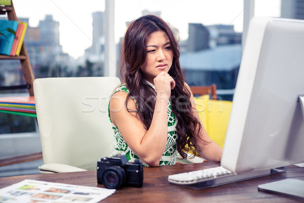Focused Asian woman using computer with hand on chin Stock photo © wavebreak_media