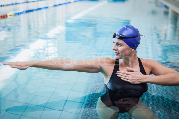Stock photo: Fit woman stretching her arms in the water