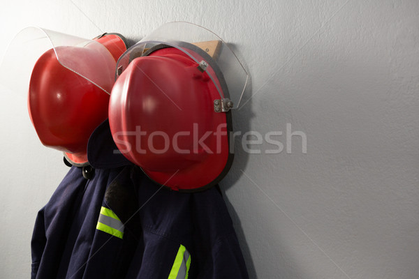 Protective workwear and hard hat hanging on hook Stock photo © wavebreak_media