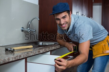 Smiling man carrying toolbox while showing ok sign  Stock photo © wavebreak_media