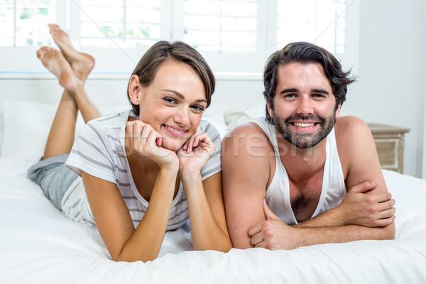 Happy couple lying on bed at home Stock photo © wavebreak_media