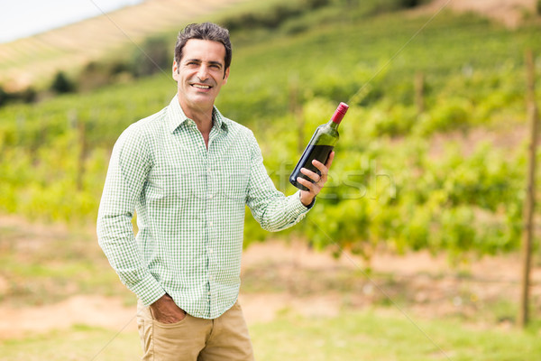 Smiling vintner holding bottle of wine Stock photo © wavebreak_media