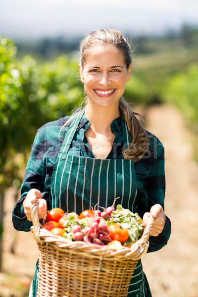Stock photo: Portrait of happy female farmer holding a basket of vegetables