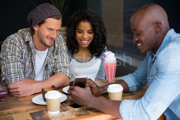 Man tonen mobiele telefoon vrienden tabel coffeeshop Stockfoto © wavebreak_media