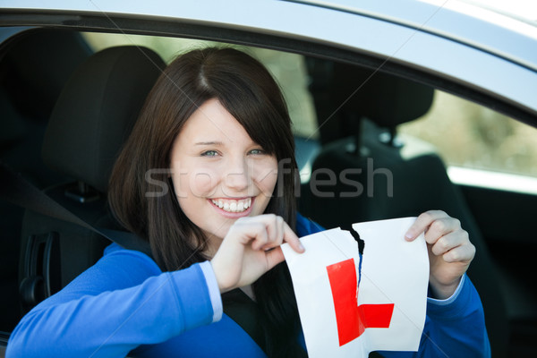 Jolly teen girl sitting in her car tearing a L-sign Stock photo © wavebreak_media