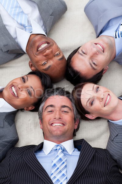 Stock photo: Smiling business team lying on the floor with heads together