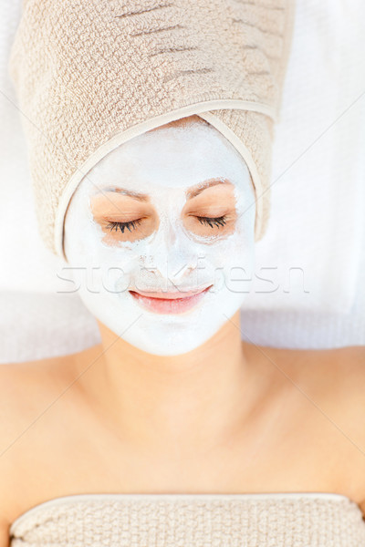 Cute young woman with closed eyes having white cream on her face lying in a spa center Stock photo © wavebreak_media