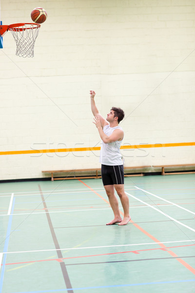 Stock photo: Good-looking man playing basketball in a gymnasium