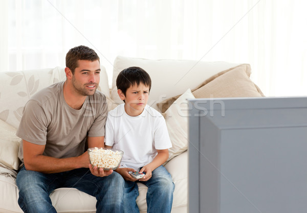Concentrated father and son watching television while eating pop corn on the sofa Stock photo © wavebreak_media