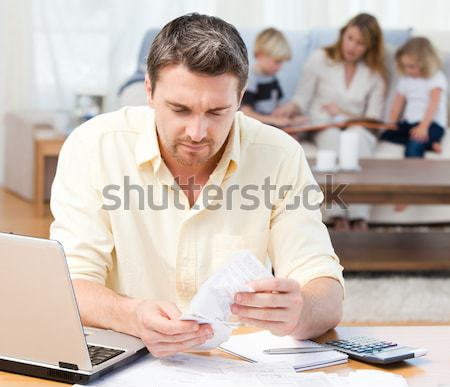 Man calculating his bills while his family are on the sofa Stock photo © wavebreak_media