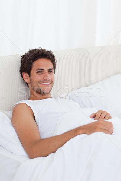 Jóképű férfi fekszik ágy otthon ház egyedül Stock fotó © wavebreak_media