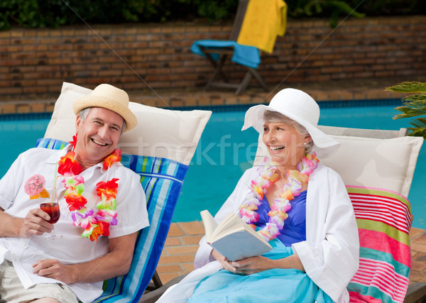 Mature woman reading a book while her husband is drinking a cocktail Stock photo © wavebreak_media