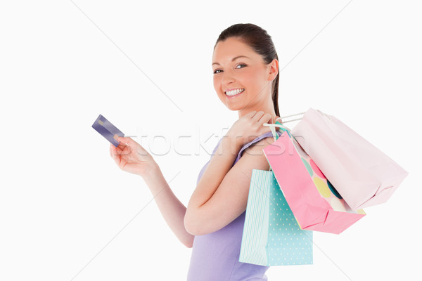 Attractive woman with a credit card holding shopping bags while standing against a white background Stock photo © wavebreak_media
