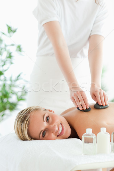 Blonde woman experiencing a stone therapy in a wellness center Stock photo © wavebreak_media