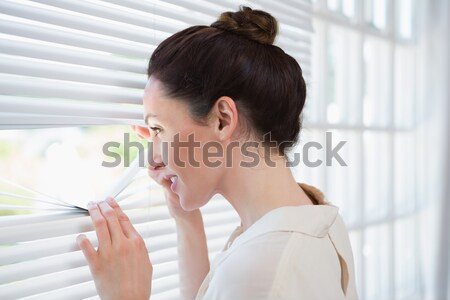 Good-looking woman peeking out a window in an office Stock photo © wavebreak_media