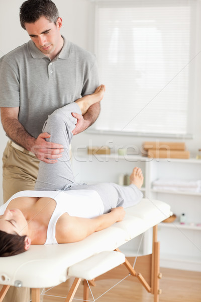 Chiropractor and patient doing exercises in a room Stock photo © wavebreak_media
