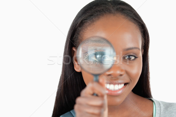 Smiling woman with magnifier against a white background Stock photo © wavebreak_media