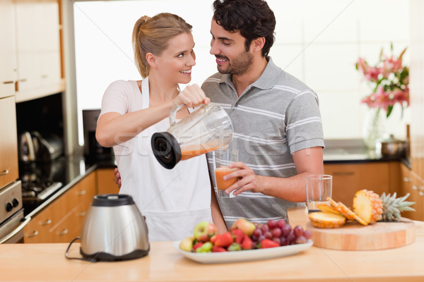 Young couple making fresh fruits juice in their kitchen Stock photo © wavebreak_media