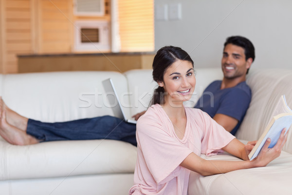 Woman reading a book while her boyfriend is using a laptop in their living room Stock photo © wavebreak_media