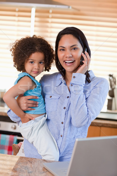 Young mother and daughter using cellphone in the kitchen together Stock photo © wavebreak_media