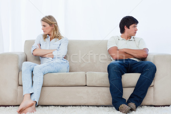 Stock photo: A angry couple sit at the two ends of the couch with their arms folded looking away