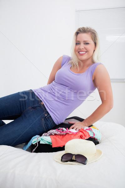 Fiatal nő zárt bőrönd ágy női mosolyog Stock fotó © wavebreak_media