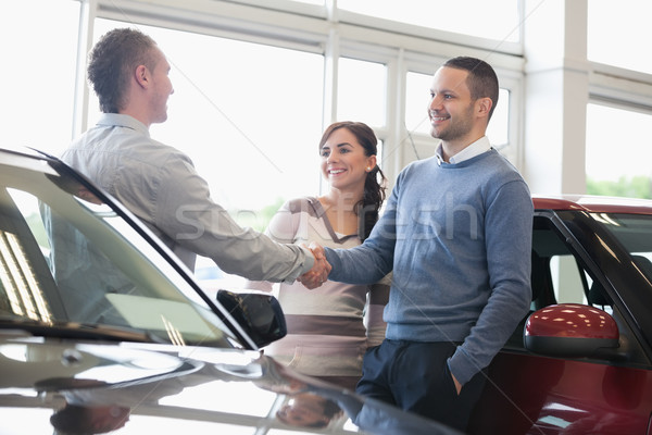 Man shaking a car dealer hand with his wife Stock photo © wavebreak_media