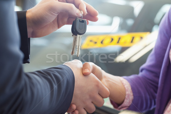 Person shaking hands in front of a sold car in a car shop Stock photo © wavebreak_media