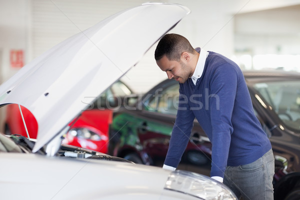 Man thinking about a car engine in a garage Stock photo © wavebreak_media