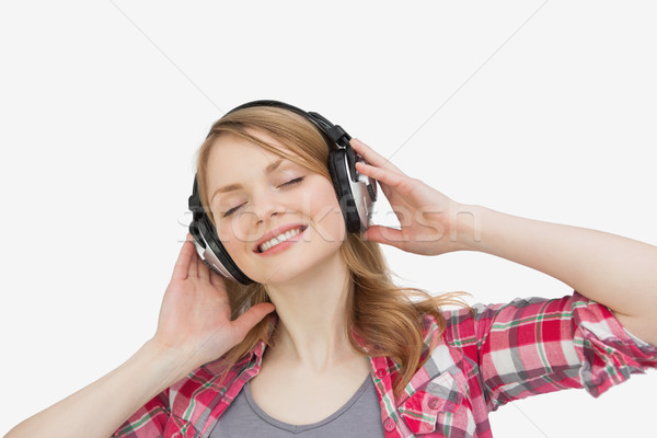Woman closing eyes while listening music against a white background Stock photo © wavebreak_media