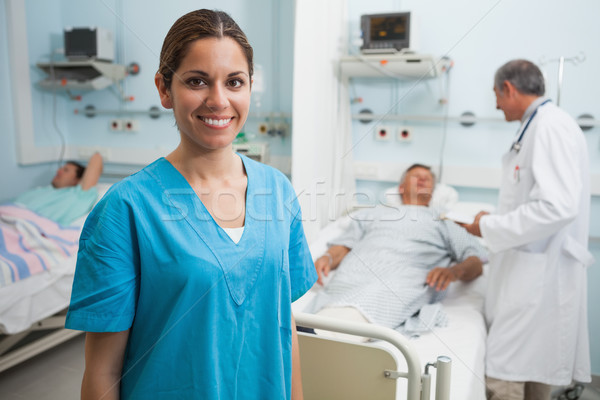 Happy nurse standing in hospital room with doctor and patient talking in background Stock photo © wavebreak_media