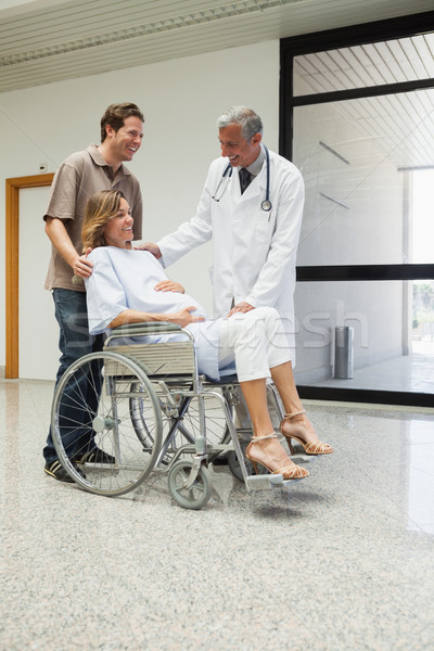 Doctor is talking to a pregnant patient in a wheelchair in the corridor of the hospital Stock photo © wavebreak_media