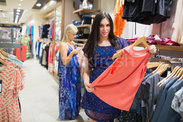 Woman is standing in a shop holding clothes  Stock photo © wavebreak_media