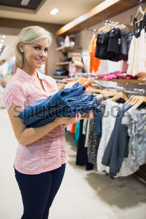 Woman standing in a shopping mall holding pants in her hands Stock photo © wavebreak_media