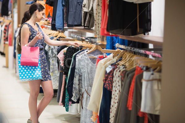 Woman searching through clothes holding two bags in clothes store Stock photo © wavebreak_media