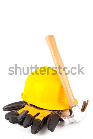 Claw hammer leaning against yellow hard hat and builder's gloves on white background Stock photo © wavebreak_media