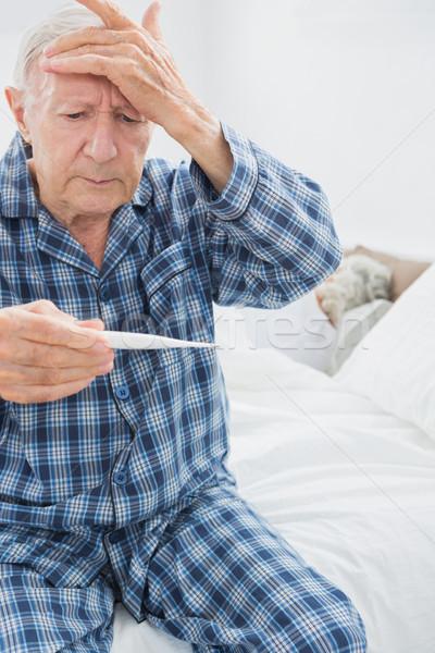 Old man taking his temperature  Stock photo © wavebreak_media
