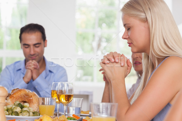 Woman saying grace with family before dinner Stock photo © wavebreak_media