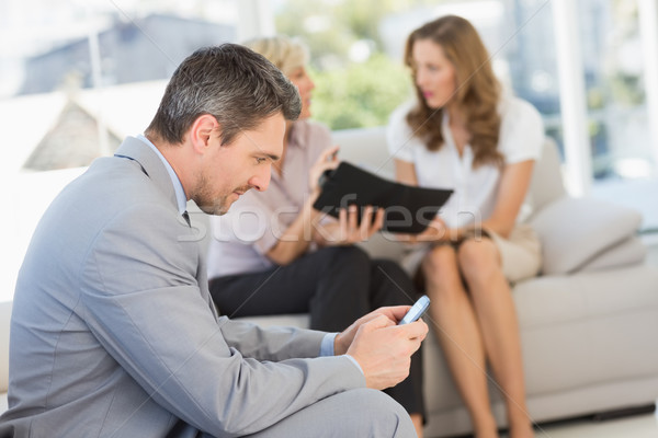 Businessman text messaging with colleagues sitting at home Stock photo © wavebreak_media